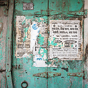Faded notice on old door in Udaipur