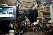 An electrician is seen in his office, as he watches a political program on TV.
