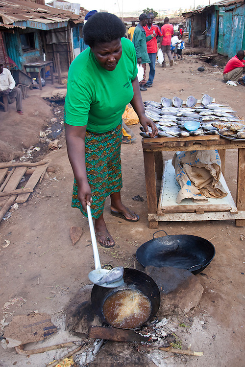 Roseline Amondi, a microloan recipient and mother of four, fries tilapia for sale at her market stall in the Kibera slum in Nairobi, Kenya.  (Roseline Amondi is featured in the book What I Eat: Around the World in 80 Diets.) MODEL RELEASED.