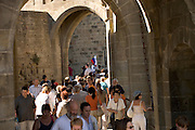 people swarming a round a tourist guide in a medieval town Europe France