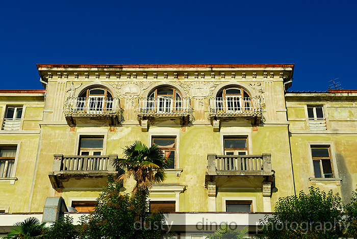 Detail of building facade with balconies, arched windows, and intricate figures in bas relief. Opatija, Croatia
