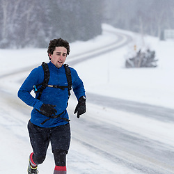 A man running on a snowy road in New Hampshire's White Mountains.