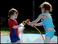 Image ©Licensed to i-Images Picture Agency. 05/07/2014. London, United Kingdom. Yasmin Attwood 4, and her brother Isaac 2, cool down in the paddling pool in the hot weather. Picture by Andrew Parsons / i-Images