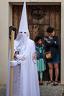 A hooded nazareno waits to restart the slow pace of the Easter day procession, while two people wait for some space to leave their home. Seville, Spain
