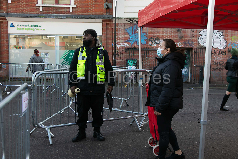 A council worker wearing a face mask lets shoppers shoppers in and out of Ridley Road Market during the second coronavirus national lockdownon on 7th November 2020, East London, United Kingdom. Only a certain number of shoppers are allowed into the market, controlled by council workers because of the corona pandemic and lockdown. The UK Government introduced a 4 week lockdown from November 5th - December 2nd to combat the coronavirus outbreak. It is the third day of the national lockdown restrictions mean that people are only allowed to meet outside, in pairs and only if keeping social distance. Only if they already live together or have formed a social bubble can they interact freely.
