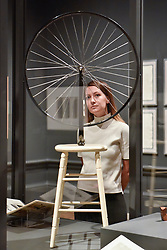 """© Licensed to London News Pictures. 03/10/2017. London, UK.  A staff member views """"Bicycle Wheel"""", 1913, 1964 edition, by Michel Duchamp at the preview of """"Dali / Duchamp"""", a new exhibition of works by Salvador Dali and Michel Duchamp taking place at the Royal Academy of Arts in Piccadilly.  Over 80 artworks in different media are on display from 7 October to 3 January 2018.   Photo credit : Stephen Chung/LNP"""