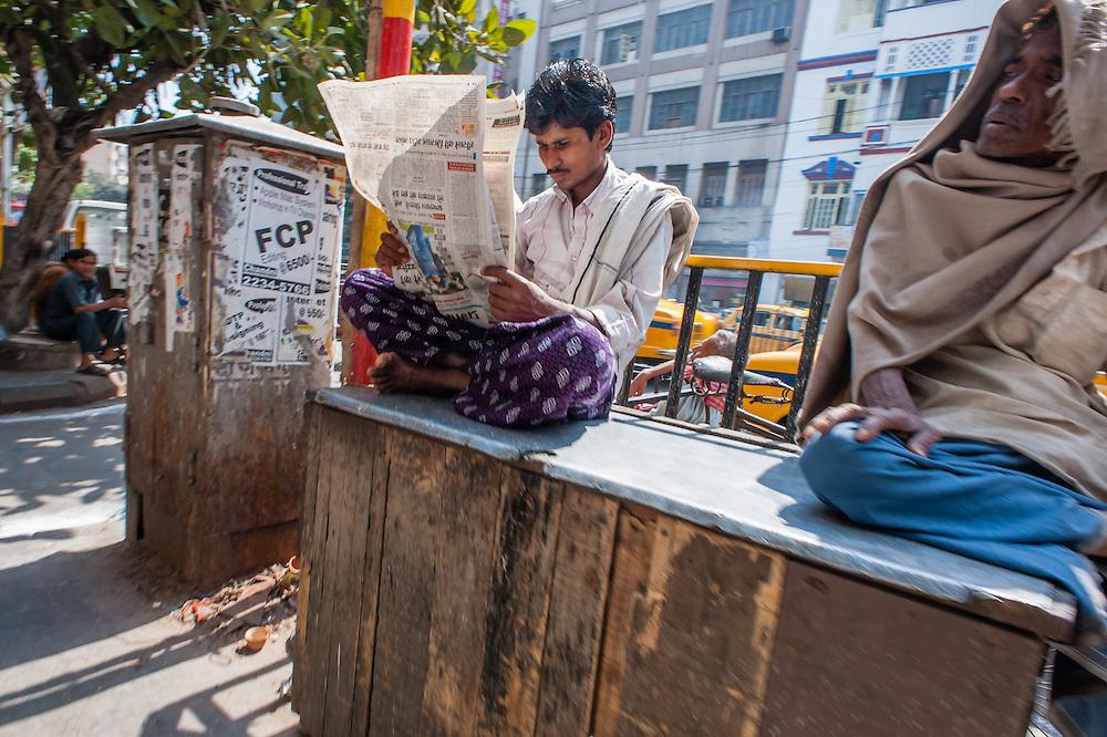 Man reading newspaper in Kolkata street (India).