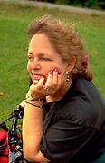 Woman age 53 resting on bicycle during Sand Lake trek.  Cumberland  Wisconsin USA