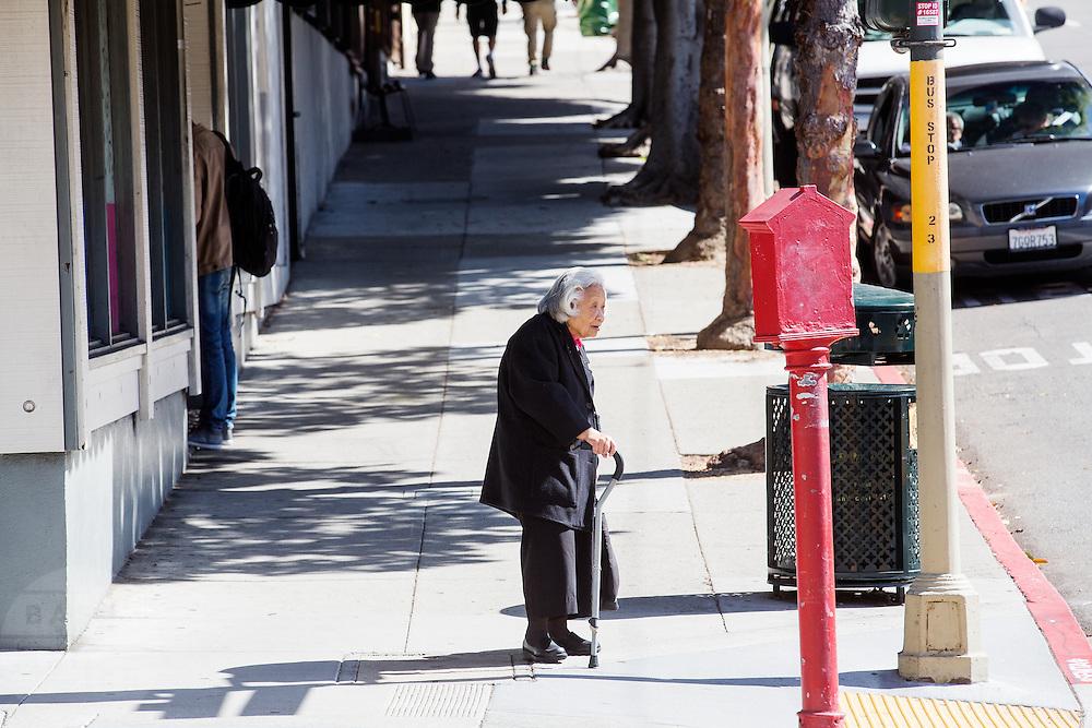 Een oudere man wacht op de stoep in Japan Town in San Francisco. De Amerikaanse stad San Francisco aan de westkust is een van de grootste steden in Amerika en kenmerkt zich door de steile heuvels in de stad.<br /> <br /> An elderly woman stands at the pavement in Japan Town in San Francisco. The US city of San Francisco on the west coast is one of the largest cities in America and is characterized by the steep hills in the city.