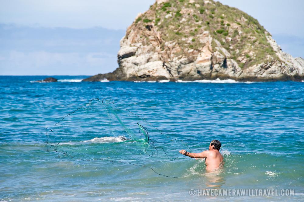 Man fising with a net at Bahia del Palmar (Palmar Bay) Ixtapa, Guerrero, Mexico