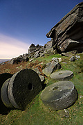 Stanage Edge's famous abandoned millstones captured by moonlight under starry skies. Gritstone formations under a full moon in Derbyshire, Peak District. England. November 2014.