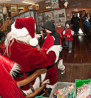Aiden McNeil meets Santa Claus with his little brother Jacob close behind at the Lakeport Freight House Museum on Saturday afternoon.  (Karen Bobotas/for the Laconia Daily Sun)