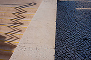 An urban landscape zigzag of shadows from the steps and handrails of Alameda Metro station, on 14th July 2016, in Lisbon, Portugal. One the sunny side are the distorted lines  of the well-trodden stairs at this main transport merge of underground train lines - and the blue tiles that act as cobbles, seen on all Portuguese streets.