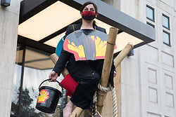 London, UK. 10 November, 2020. An environmental activist from Extinction Rebellion holds a bucket of fake oil during a protest outside the Shell Centre to mark the 25th anniversary of the killings of the Ogoni Nine. The Ogoni Nine, leaders of the Movement for the Survival of the Ogoni People (MOSOP), were executed by the Nigerian government in 1995 after having led a series of peaceful marches involving an estimated 300,000 Ogoni people against the environmental degradation of the land and waters of Ogoniland by Shell and to demand both a share of oil revenue and greater political autonomy.