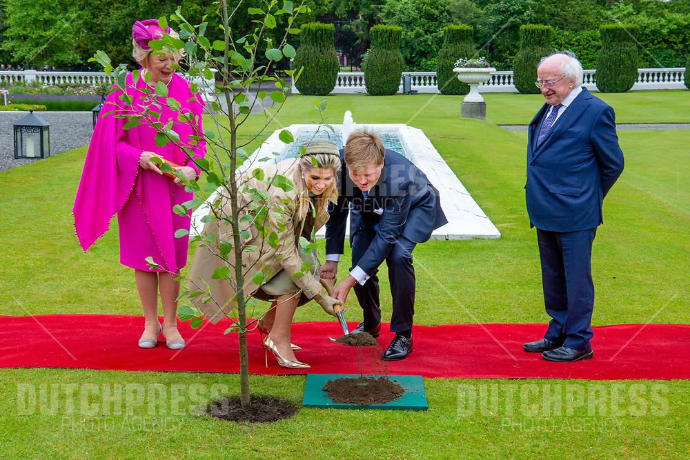 Koning Willem-Alexander en koningin Maxima met president Michael Higgins en zijn vrouw Sabina tijdens het planten van een boom in het Presidentieel Paleis Aras an Uachtarain in Dublin, op dag 1 van het 3-daags staatsbezoek van het Nederlands Koningspaar aan Ierland.