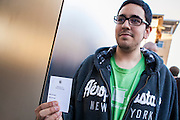 16 MARCH 2012 - SCOTTSDALE, AZ:  SCOTT BERLIN, from Tempe, AZ, shows off the card that guarantees him a New iPad at the Apple Store in Scottsdale. Several hundred people were in line at the Apple Store in the Scottsdale Quarter in Scottsdale, AZ, Friday to buy the New iPad.    PHOTO BY JACK KURTZ
