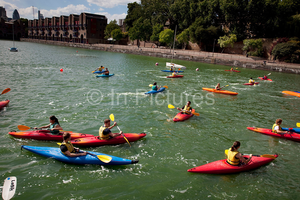 Young people messing around in the water during summer activities in Shadwell Basin in East London. This is a centre where the water is used by youth of all ages. Here the kayak club is having fun and playing games amongst each other.