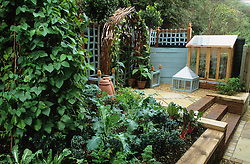 Raised vegetable bed. Small lean to coldframe with cloche. Mirrored archway.