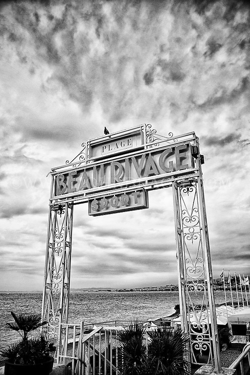 Black and white view of the Plage Beau Rivage Sport Hotel and Restaurant sign, and Bay of Angels found along the Promenade des Anglais, Nice, France.