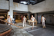 Workers use bamboo poles to lift and to open up a steam vat ahead of alcohol extraction at a baijiu production facility that is part of the Shuijingfang museum, operated by Sichuan Swellfun Co., a unit of Diageo Plc in Chengdu, China, on Tuesday, Sept. 20, 2016. With less than 1 percent of baijiu, or white liquor, consumed abroad, Chinese distillers want to transform the fiery Chinese grain liquor into the new tequila for Americans and Europeans.