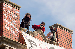 © Licensed to London News Pictures; 04/06/2021; Bristol, UK. Squatters can be seen with banners and graffiti on the tower of the former Salvation Army building on Dean Lane in Bedminster as police mounted a major operation to enter the squat and arrested 3 people suspected of criminal activity connected with the squatted occupation of buildings in High Street in Bristol city centre which was repossessed earlier this morning by Bailiffs accompanied by around 100 police, but those occupying the buildings in High Street had already left. Those arrested at the Salvation Army building are a 40-year-old man on suspicion of assaulting an emergency worker and escaping lawful custody, a 26-year-old man on suspicion of assaulting an emergency worker and escaping lawful custody, and a woman on suspicion of affray. Police were not evicting the Salvation Army building on Dean Lane as they do not have powers to do so. Photo credit: Simon Chapman/LNP.