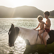 Two brothers stand on the back of a black and white horse, in the water (lake).