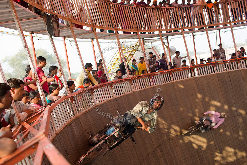 For entertainment, a crowd is observing stuntmen driving motorbikes in a pit, during the yearly Sonepur Mela, Asia's largest cattle market, in Bihar, India.