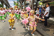 """05 JULY 2014 - BANGKOK, THAILAND:  School children on Sukhumvit Road in Bangkok during a parade for vassa. Vassa, called """"phansa"""" in Thai, marks the beginning of the three months long Buddhist rains retreat when monks and novices stay in the temple for periods of intense meditation. Vassa officially starts July 11 but temples across Bangkok are holding events to mark the holiday all week.   PHOTO BY JACK KURTZ"""