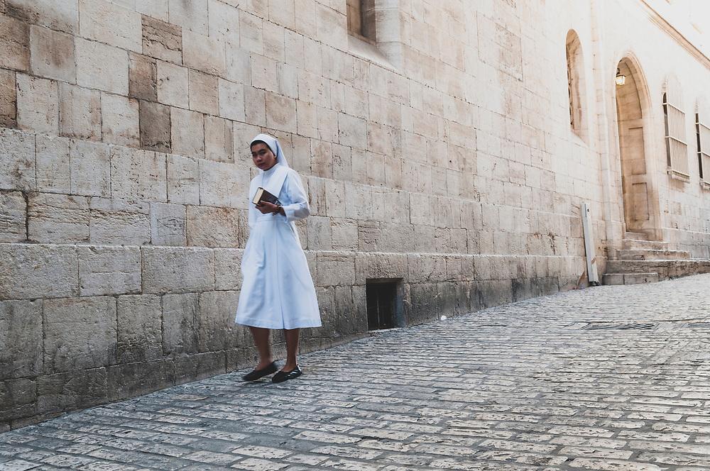 A nun walks on the Via Dolorosa in the Muslim Quarter of Jerusalem's Old City on October 20, 2010.