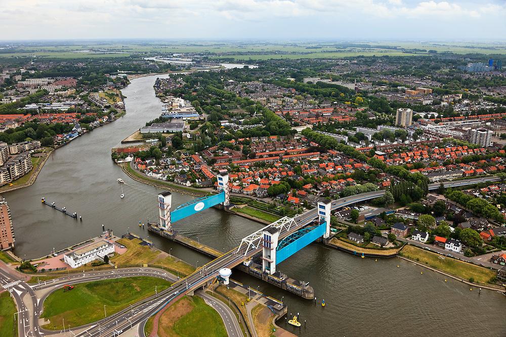 Nederland, Zuid-Holland, Capelle aan den IJssel, 22-05-2011. Stormvloedkering in de Hollandsche IJssel. Bij storm en dreigend hoog water wordt een van de twee schuiven naar beneden gelaten, de tweede schuif dient als reserve. De scheepvaart kan de gesloten kering paseren via de naastgelegen schutsluis. Rechts van de rivier Krimpen aan den IJssel. De stormvloedkering maakt deel uit van de Deltawerken en is als eerste voltooid in 1958. Ten tijde van De Ramp - watersnood 1953 - werd het zeewater door de storm opgestuwd en dreigde de verzwakte rivierdijken in het achterland het te begeven waardoor grote van het laag gelegen westen van Nederland ondergelopen zouden zijn..Capelle at the river IJssel, near Rotterdam: storm surge barrier, protects the highly populated western part of Holland, which lies below sea level. In case of storm and threat of high water, one of the two doors is lowered into the river (the second door is a spare one). The lock next to the barrier allows shipping when the barrier is closed ..luchtfoto (toeslag); aerial photo (additional fee required);.foto Siebe Swart / photo Siebe Swart