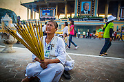 """30 JANUARY 2013 - PHNOM PENH, CAMBODIA: A Cambodian woman wearing white mourning clothing burns incense for late Cambodian King Norodom Sihanouk in Phnom Penh. Sihanouk (31 October 1922- 15 October 2012) was the King of Cambodia from 1941 to 1955 and again from 1993 to 2004. He was the effective ruler of Cambodia from 1953 to 1970. After his second abdication in 2004, he was given the honorific of """"The King-Father of Cambodia."""" Sihanouk held so many positions since 1941 that the Guinness Book of World Records identifies him as the politician who has served the world's greatest variety of political offices. These included two terms as king, two as sovereign prince, one as president, two as prime minister, as well as numerous positions as leader of various governments-in-exile. He served as puppet head of state for the Khmer Rouge government in 1975-1976. Most of these positions were only honorific, including the last position as constitutional king of Cambodia. Sihanouk's actual period of effective rule over Cambodia was from 9 November 1953, when Cambodia gained its independence from France, until 18 March 1970, when General Lon Nol and the National Assembly deposed him. Upon his final abdication, the Cambodian throne council appointed Norodom Sihamoni, one of Sihanouk's sons, as the new king. Sihanouk died in Beijing, China, where he was receiving medical care, on Oct. 15, 2012. His cremation is scheduled to take place on Feb. 4, 2013. Over a million people are expected to attend the service.        PHOTO BY JACK KURTZ"""