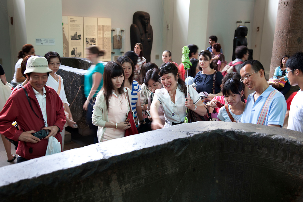 The British Museum, London. Chinese visitors are shown around the ancient Egyptian rooms by their tour guide.