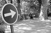 Black and white photo of man reading newspaper in park in Granada, Spain.
