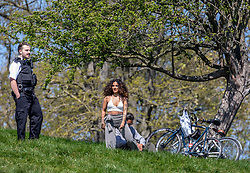 © Licensed to London News Pictures. 19/04/2020. London, UK. A policeman speaks to two members of the public with bikes as Police patrol Primrose Hill enforcing lockdown rules on social distancing and exercise as Ministers urge councils to keep parks open to the public during lockdown. Photo credit: Alex Lentati/LNP