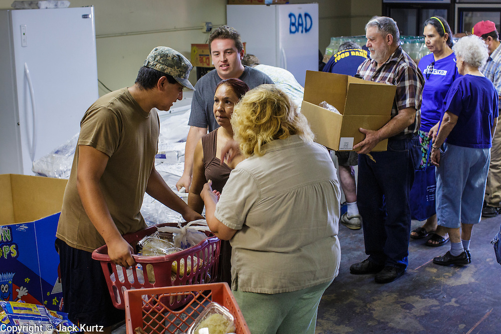 07 AUGUST 2012 - TOLLESON, AZ:   Clients pick up meals at the food bank in Tolleson, AZ, about 15 miles west of Phoenix. The Tolleson food bank has been operating for more than 20 years. It used to serve mostly the families of migrant farm workers that worked the fields around Tolleson but in the early 2000's many of the farms were sold to real estate developers. Now the food bank serves both farm worker families and people who lost their homes in the real estate crash, that his Phoenix suburbs especially hard. More than 150 families a day are helped by the Tolleson food bank, an increase of more than 50% in the last five years.  PHOTO BY JACK KURTZ
