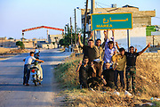 """A youth group of local residents who also serve as armed members of the Free Syrian Army (FSA) take a moment to pose with a two-finger salute in front of the """"Marea"""" sign as they went out for a walk freely around the outskirts on Wednesday, June 27, 2012 - as they play and salute with two fingers ahead of their swimming pool day after the night shift in guarding Marea on Wednesday, June 27, 2012. (Photo by Vudi Xhymshiti)"""