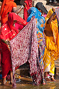 Indian Hindu pilgrims bathing in The Ganges River at Darbhanga Ghat in Holy City of Varanasi, Benares, India