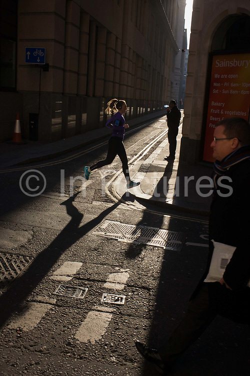 A woman jogger runs past a male exhaling smoke from his cigarette, on the corner of Lombard Street and Abchurch Lane, EC4, in the City of London. Caught in the narrow sunlight along this narrow lane in the heart of the capital's financial district (aka The Square Mile) we see the female runner in mid-air as she passes the man exhaling his plume of blue smoke. Another stranger is about to walk past, a businessman on his way along Lombard Street in this, the oldest part of London. Strong shadows can be seen on the walls of this narrow medieval lane, first mentioned as Abbechurche Lane in 1291.