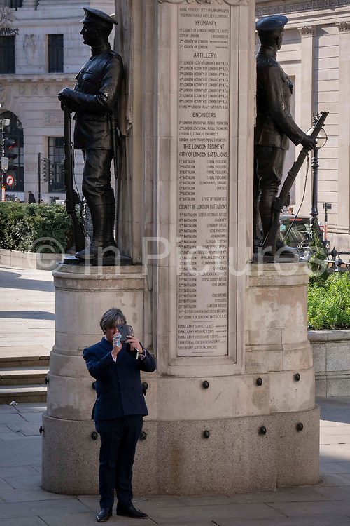 A businessman pauses to photograph beneath the WW1 war memorial at Bank during a much quieter evening rush-hour during the third lockdown of the Coronavirus pandemic. Financial institutions and the Bank of England are located here, in the heart of the City of London, aka Square Mile, on 9th March 2021, in London, England.
