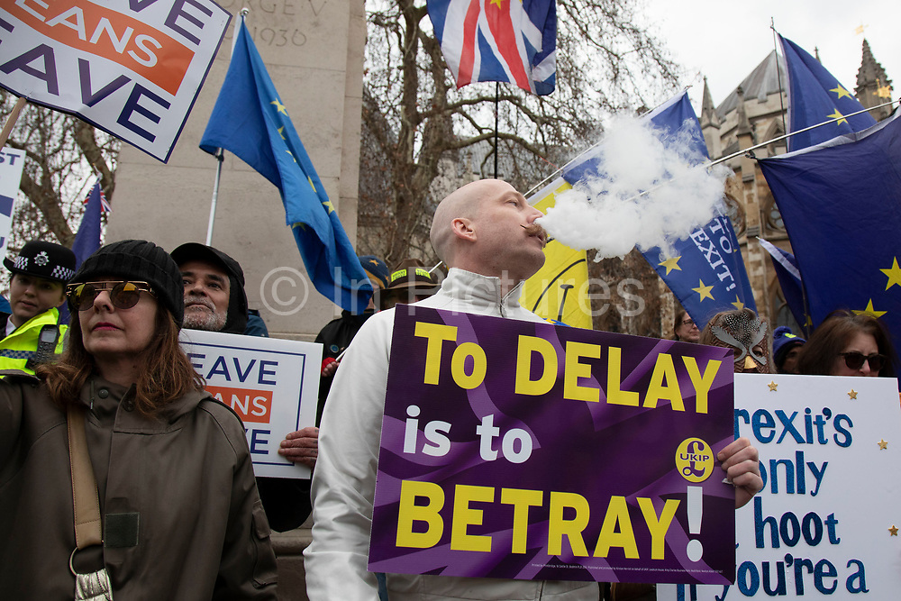 Leave means leave pro Brexit anti Europe demonstrator blowing vape smoke protests with a to delay is to betray placard in Westminster opposite Parliament on the day MPs vote on EU withdrawal deal amendments on 29th January 2019 in London, England, United Kingdom.