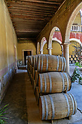 Oak barrels filled with Mezcal age under the derelict arches of the Hacienda de Jaral de Berrio in Jaral de Berrios, Guanajuato, Mexico. The abandoned Jaral de Berrio hacienda was once the largest in Mexico and housed over 6,000 people on the property and is credited with creating Mescal.