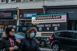 © Licensed to London News Pictures. 23/12/2020. London, UK. A huge coronavirus alert sign warning members of the public to be vigilant appears in Putney, South West London as Health Secretary Matt Hancock announced in a televised address to the Nation this afternoon that yet another new Covid-19 mutation has been discovered in South Africa and is already in the UK as Downing Street orders many more areas of England to go into Tier 4. Tougher Covid-19 restrictions have already been implemented in London after the UK mutated strain continues to spread throughout the South East . Photo credit: Alex Lentati/LNP
