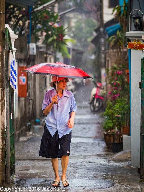 27 MARCH 2016 - BANGKOK, THAILAND: A woman walks through the rain to Easter services at Santa Cruz Church in Bangkok. Santa Cruz was one of the first Catholic churches established in Bangkok. It was built in the late 1700s by Portuguese soldiers allied with King Taksin the Great in his battles against the Burmese who invaded Thailand (then Siam). There are about 300,000 Catholics in Thailand, in 10 dioceses with 436 parishes. Easter marks the resurrection of Jesus after his crucifixion and is celebrated in Christian communities around the world.      PHOTO BY JACK KURTZ
