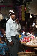 Man smoking a cheroot (Burmese cigar) while waiting in a market in Bagan, Myanmar.