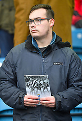 A fan in the stands holding the matchday programme