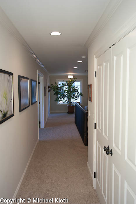 Hallway leading to upstairs bedroom.  The closet on right is very large (wide and deep) with custom shelving.
