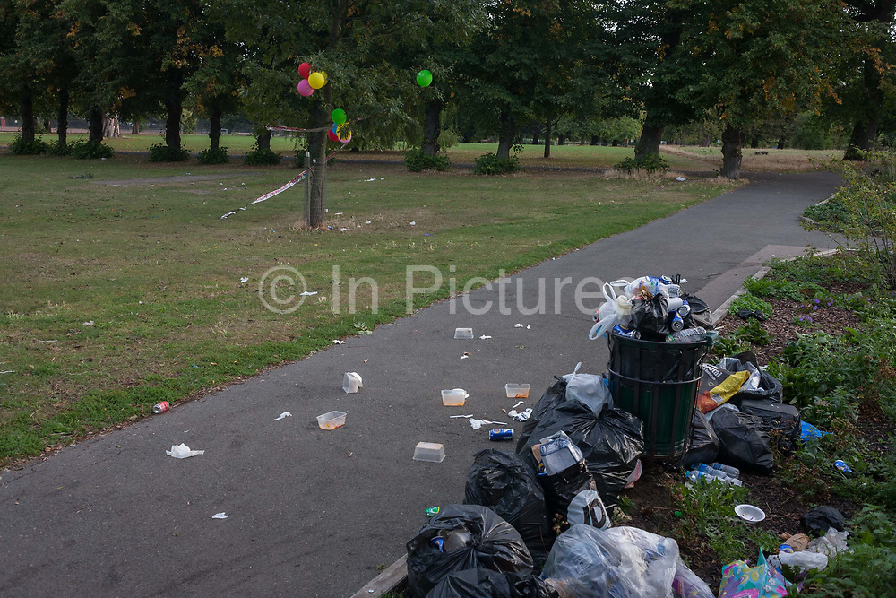 A bin overflows with refuse and litter in a public space with discarded birthday party balloons left tied in a tree in Ruskin Park, south London borough of Lambeth, UK. The park no longer has proper funding nor is staffed by the full compliment of council employees to ensure bins are emptied and trees properly maintained.