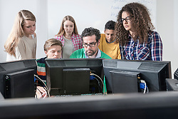 Teacher teaching students in computer lab, Bavaria, Germany