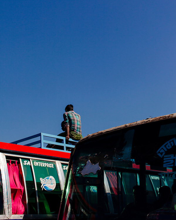 Man travelling on top of a bus