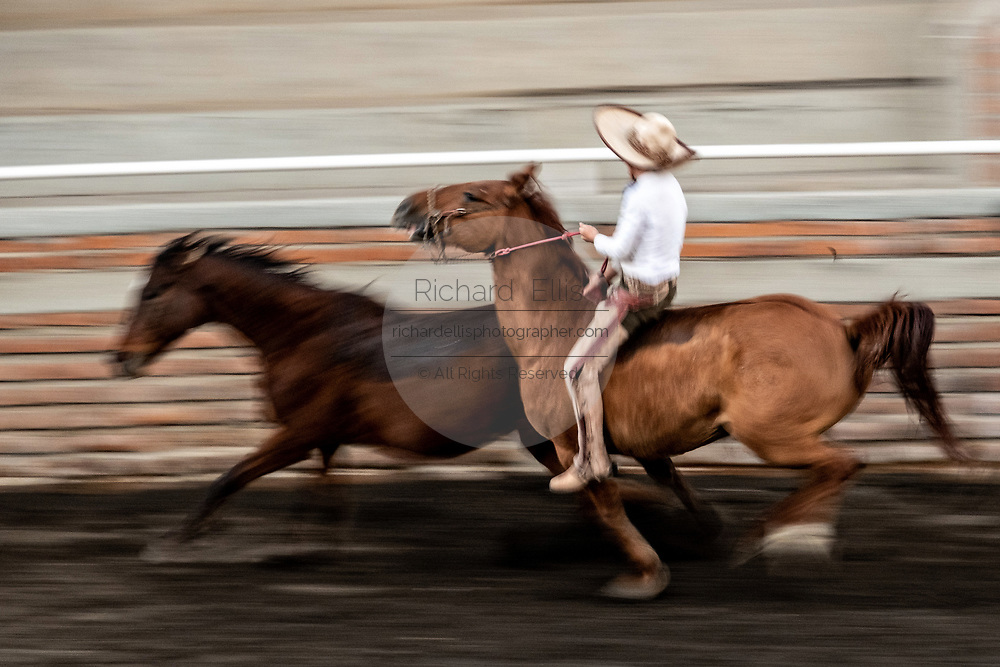 Young Juan Franco, from the legendary Franco family of Charro champions, practices leaping bareback from one horse to another in an event called the The Pass of Death during a family practice session in the Jalisco Highlands town of Capilla de Guadalupe, Mexico.  The event involves riding bareback and then leaping from one horse to the bare back of a loose, unbroken horse without reins and ride it until it stops bucking.